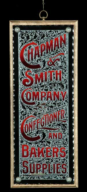Chapman & Smith Co. sign is a replica of an old Rawson & Evans sign. The sign is on scalloped edged glass and is glue chipped and silvered with blended letters mounted on a decorative wood panel.